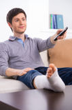 Man watching TV in bandage. Young man watching TV in bandage on sofa Stock Image