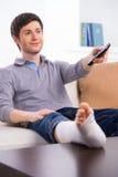 Man watching TV in bandage stock image