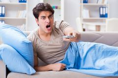 The man watching tv from bed holding remote control unit. Man watching tv from bed holding remote control unit Stock Images
