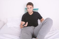 Man watching tv on bed. Royalty Free Stock Photography