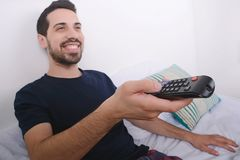 Man watching tv on bed. Portrait of young man watching tv and relaxed on bed. Indoors Royalty Free Stock Photography