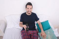 Man watching tv on bed. Portrait of young man watching tv and relaxed on bed. Indoors Stock Photography