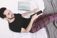 Man watching tv on bed. Portrait of young man watching tv and relaxed on bed. Indoors Royalty Free Stock Images