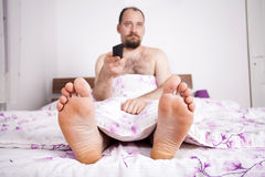 Man watching TV from the bed with remote-control Royalty Free Stock Photography