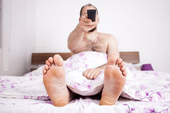 Man watching TV from the bed with remote-control Royalty Free Stock Image