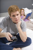 Man Watching TV In Bedroom. Young men watching TV with women reading novel in bedroom Stock Photo