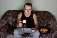 Man watching tv with beer Stock Photography