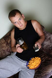 Man watching tv with beer and chips Royalty Free Stock Photography