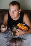 Man watching tv with beer and chips. Young man watching tv with beer and chips Stock Photos