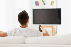 Man watching tv and changing channels at home. Leisure, technology, mass media and people concept - man watching tv and changing channels at home from back Stock Image