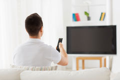 Man watching tv and changing channels at home Royalty Free Stock Images