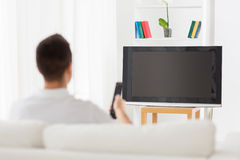 Man watching tv and changing channels at home. Leisure, technology, mass media and people concept - man watching tv and changing channels at home from back Royalty Free Stock Photography