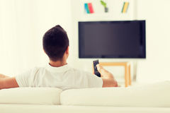 Man watching tv and changing channels at home Stock Image