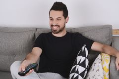 Man watching tv on couch. Attractive young man watching tv and relaxed on couch. Indoors Royalty Free Stock Photos