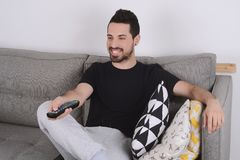 Man watching tv on couch. Attractive young man watching tv and relaxed on couch. Indoors Royalty Free Stock Images