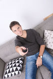 Man watching tv on couch. Attractive young man watching tv and relaxed on couch. Indoors Stock Photos