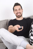 Man watching tv on couch. Attractive young man watching tv and relaxed on couch. Indoors Royalty Free Stock Photography