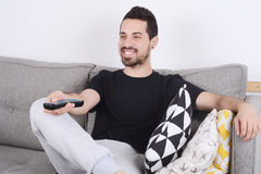 Man watching tv on couch. Attractive young man watching tv and relaxed on couch. Indoors Stock Photo