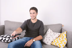 Man watching tv on couch. Attractive young man watching tv and relaxed on couch. Indoors Royalty Free Stock Photo