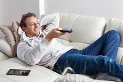 Man watching tv. At cozy modern apartment Stock Images