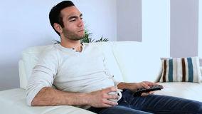 Man watching tv with a cup of coffee stock footage