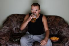Man watching tv and drinking beer Stock Images