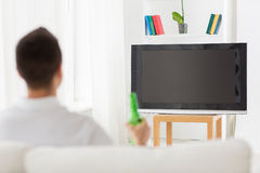 Man watching tv and drinking beer at home Royalty Free Stock Images