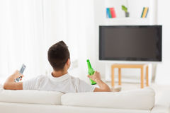 Man watching tv and drinking beer at home Royalty Free Stock Photography