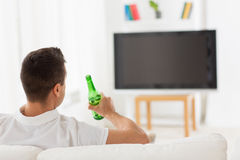 Man watching tv and drinking beer at home. Leisure, technology, mass media and people concept - man watching tv and drinking bottle beer at home from back Royalty Free Stock Photos
