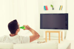 Man watching tv and drinking beer at home Royalty Free Stock Image