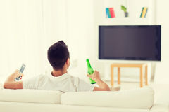 Man watching tv and drinking beer at home Stock Images