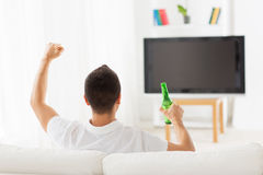Man watching tv and drinking beer at home Royalty Free Stock Photos