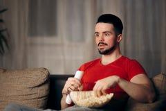 Man Watching TV Eating Pop Corn royalty free stock photography