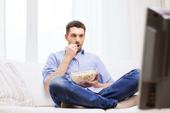 Man watching tv and eating popcorn at home Stock Photos