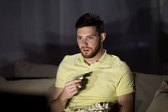 Man watching tv and eating popcorn at night Royalty Free Stock Photography