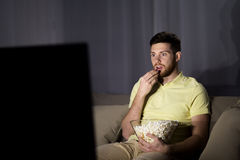 Man watching tv and eating popcorn at night. People, mass media, television and entertainment concept - young man watching tv and eating popcorn at night at home Stock Photo