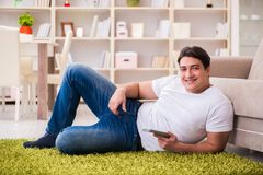 The man watching tv at home on floor. Man watching tv at home on floor Stock Image