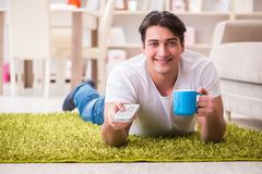 The man watching tv at home on floor. Man watching tv at home on floor Stock Photo