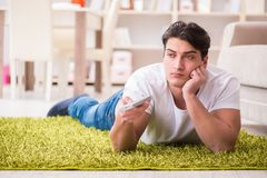 The man watching tv at home on floor. Man watching tv at home on floor Stock Images