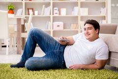 The man watching tv at home on floor. Man watching tv at home on floor Stock Photography