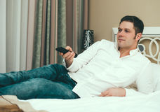 Man watching TV. Man watching TV in hotel room Royalty Free Stock Photo
