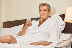 Man watching TV in hotel room Stock Image