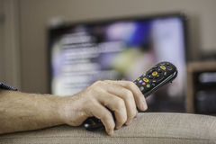 Man watching TV. Man keeping a TV remote while watching a television program Stock Photography