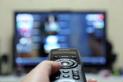 A man watching TV. Left hand holding a remote Stock Photography