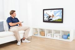 Man watching tv in living room Royalty Free Stock Image
