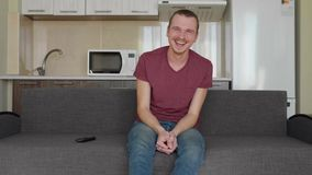 A man is watching TV. A cheerful young guy sitting on the couch and laughs hard. A kitchen on the background. 4K footage stock video footage