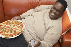 Man Watching TV With Pizza On Lap Stock Image