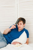 Man watching TV sitting on the bed eating popcorn Royalty Free Stock Images
