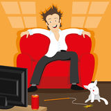 A man watching TV. A man sitting on the couch and watching TV Stock Image