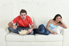 Man watching tv sport football game with man excited and concentrated ignoring wife Stock Photos
